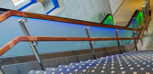 Speciaal trapleuning gemaakt van RVS en hout in metrostation